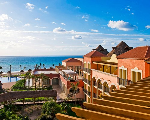 An exterior view of Ocean Coral & Turquesa resort alongside the ocean.