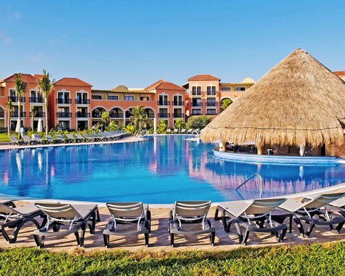 An outdoor swimming pool with chaise lounge chairs and swim up bar alongside the resort.