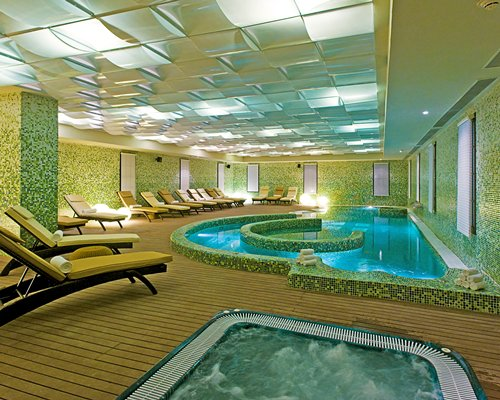 An indoor hot tub and swimming pool with chaise lounge chairs.