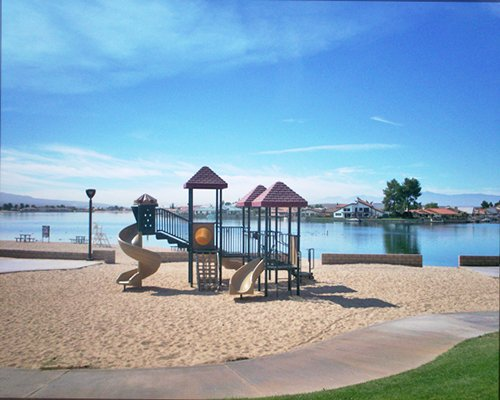 Kids playscape with a slide alongside the lake.