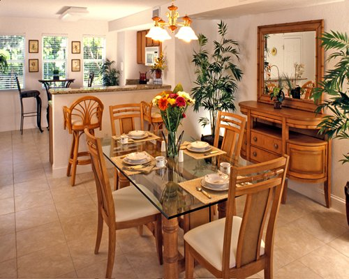 An open plan kitchen with breakfast bar glass top dining table and outside view.