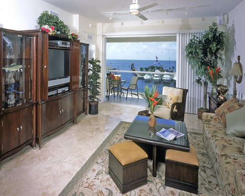 A well furnished living room with a television balcony patio furniture and ocean view.