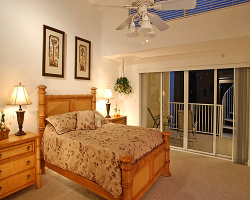 A well furnished bedroom with a balcony and patio furniture.