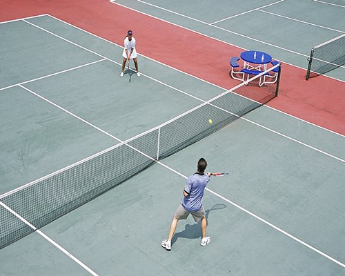 A couple playing the outdoor tennis alongside the patio furniture.