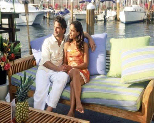 A couple in the boat alongside a marina.