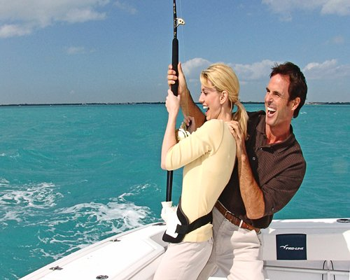 A couple at a boat fishing in the ocean.