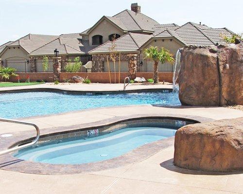 An outdoor swimming pool with hot tub alongside the resort units.