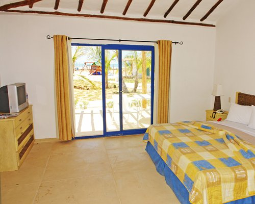 A well furnished bedroom with a king bed and outdoor view.