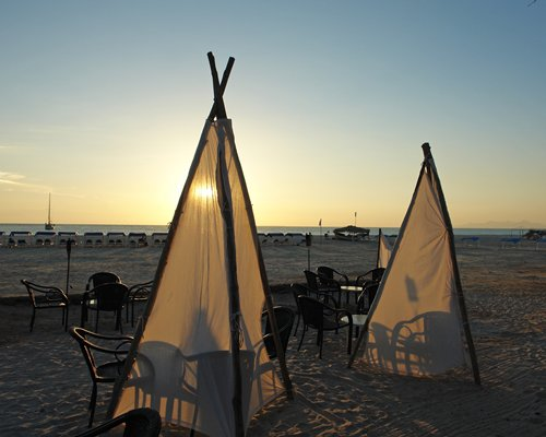 A view of the teepee with patio furniture on the shore at dusk.