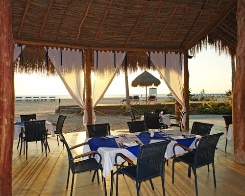 An outdoor fine dining area alongside the beach with chaise lounge chairs and thatched sunshade.