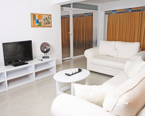 A well furnished living room with double pull out sofas and a television.