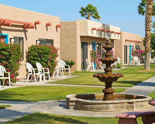 Exterior view of the units with patio chairs and fountain.