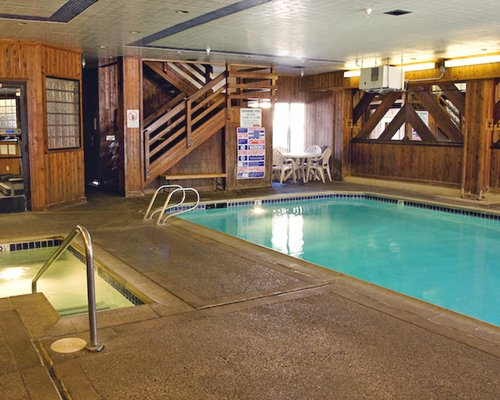 An indoor swimming pool with hot tub and patio alongside a stairway.