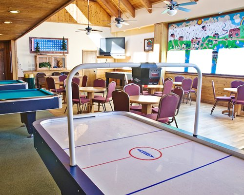 An indoor recreation room with air hockey table ping pong and outside view.