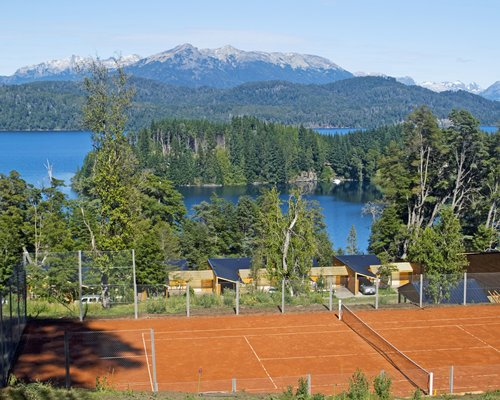 Outdoor tennis courts alongside the lake surrounded by wooded area.