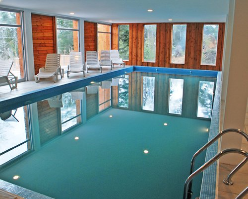 An indoor swimming pool with chaise lounge chairs and an outside view.