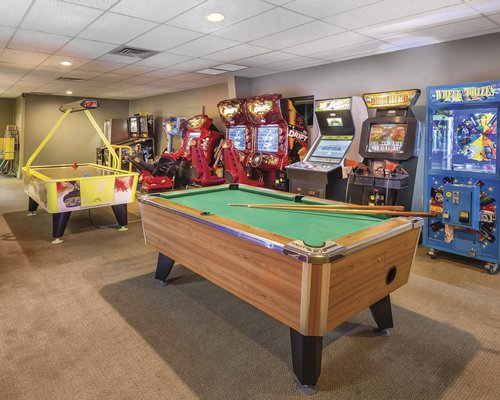 An indoor recreational area with pool table air hockey table and arcade games.