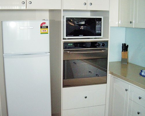 A kitchen with a refrigerator and oven.