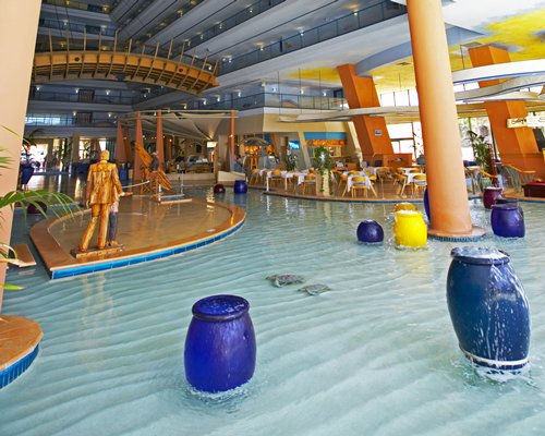An indoor pool with water features alongside a fine dining restaurant.