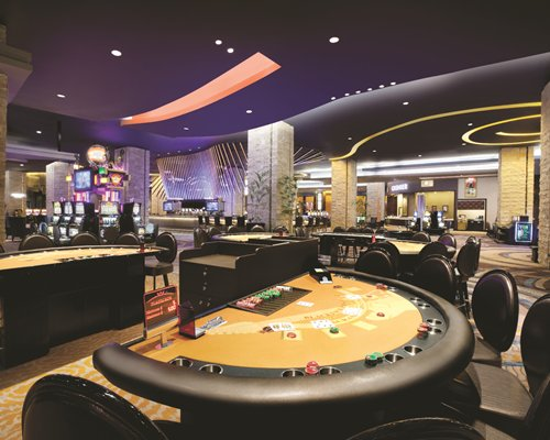 Indoor recreation room with casino tables and arcade games.