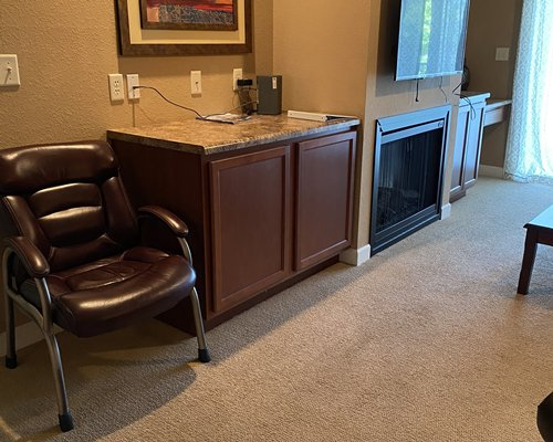 A well furnished living room with a television and a balcony with patio.