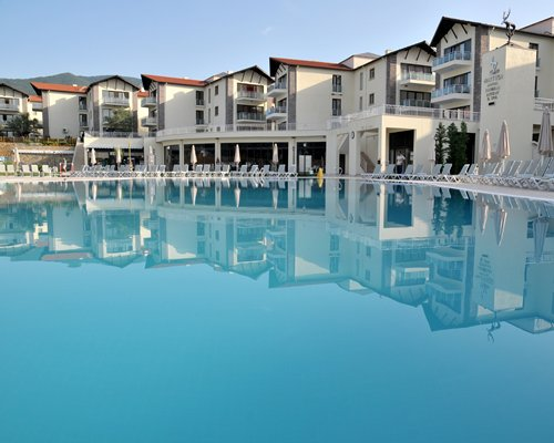 Exterior view of Hattusa VTC Kazdaglari with large outdoor swimming pool chaise lounge chairs and sunshades.