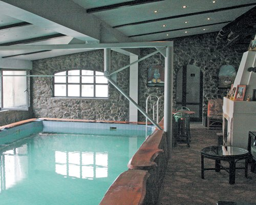 Indoor swimming pool with a fireplace.
