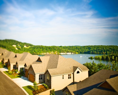 Scenic exterior view of units at The Cliffs at Long Creek alongside the lake surrounded by wooded area.