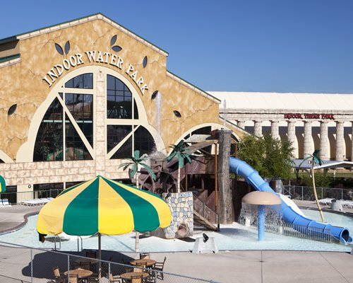 Exterior view of an indoor water park with patio and sunshade.