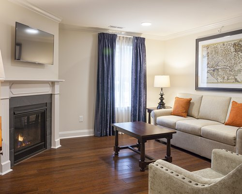 A well furnished living room with a television and fire in the fireplace.