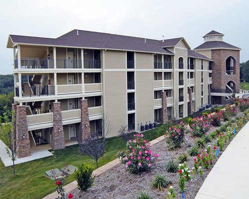 A scenic exterior view of multi story units with flowering shrubs.