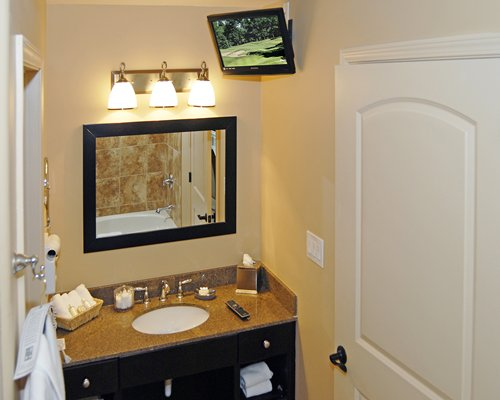 A single sink vanity with television.