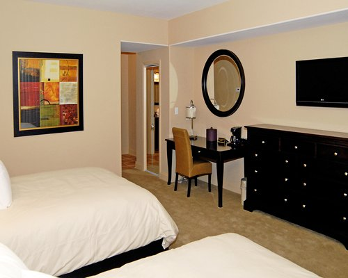 A well furnished bedroom with two beds and vanity.