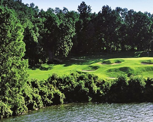 Gold course alongside the lake surrounded by wooded area.