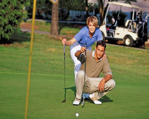 A couple playing golf on the golf course.