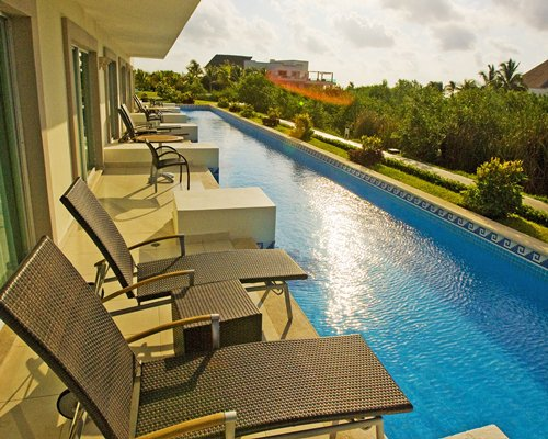 A large outdoor swimming pool with chaise lounge chairs.