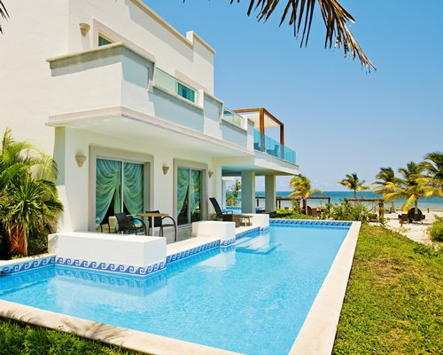 Exterior view of a unit with outdoor swimming pool and patio chairs alongside the sea.