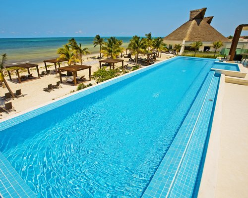 Large outdoor swimming pool alongside the beach with gazebos chaise lounge chairs and palm trees.
