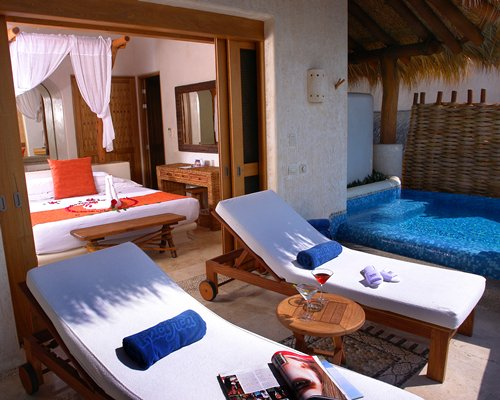 View of chaise lounge chairs and a pool alongside the bedroom.