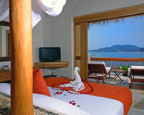 A well furnished bedroom with a king bed television and balcony.