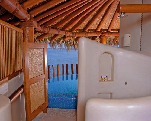 A bathroom with a shower and view of outdoor swimming pool alongside the ocean.