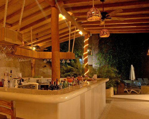 An outdoor bar with chaise lounge chairs.