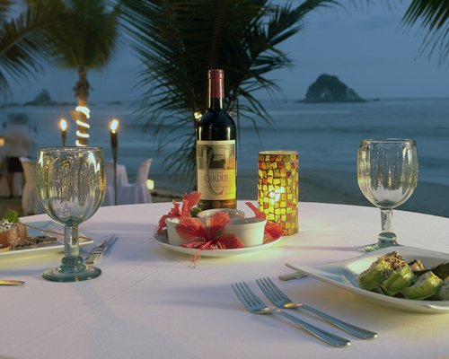 A view of food and beverages on a table with the ocean view.