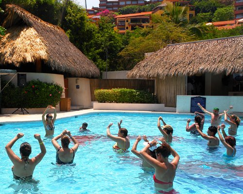 View of people exercising at an outdoor swimming pool alongside thatched units.