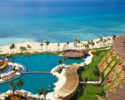 An aerial view of the large outdoor pool at Grand Velas Riviera Maya resort .