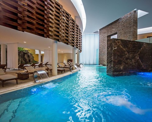 Indoor swimming pool with chaise lounge chairs.