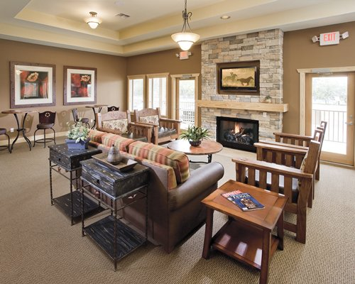 A well furnished indoor lounge area with a fire in the fireplace.
