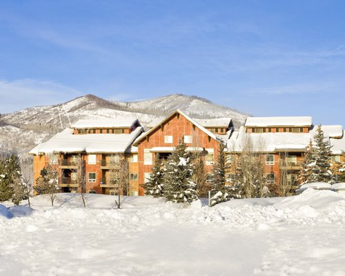 An exterior view of the resort alongside the mountains covered in snow.