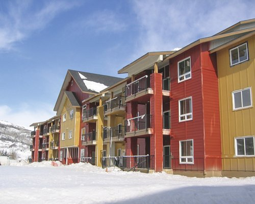 An exterior view of multi story resort units covered in snow.