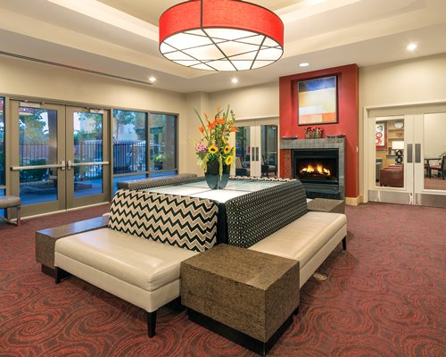 A well furnished lobby lounge with fire in the fireplace and outside view.